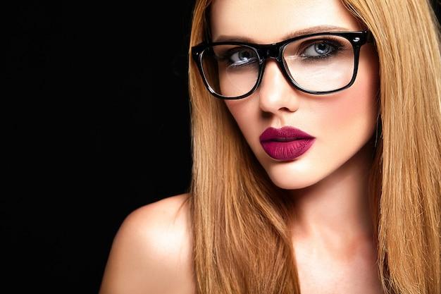 Sinnliches glamourporträt des schönen blonden frauenmodells mit frischem täglichem make-up mit lila lippenfarbe und sauberer gesunder haut in gläsern Kostenlose Fotos