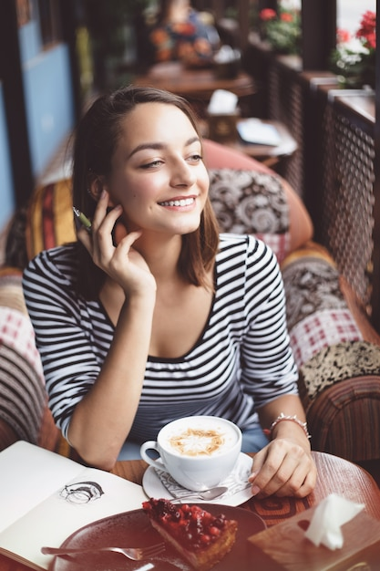 Sitzen der jungen frau innen im städtischen café Kostenlose Fotos