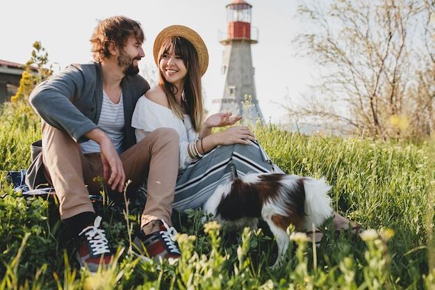 Sitzen im gras junge stilvolle hipster-paar in der liebe mit hund in der landschaft, sommer-stil boho mode, romantisch Kostenlose Fotos