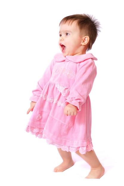 Sitzen lachendes hübsches kleines einjähriges baby mit offenem mund im rosa kleidspaß, der zeh hält Premium Fotos
