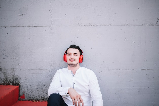 Sitzender mann, der kopfhörer verwendet Kostenlose Fotos