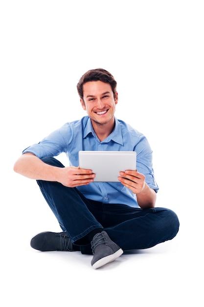 Sitzender mann mit einem digitalen tablet Kostenlose Fotos