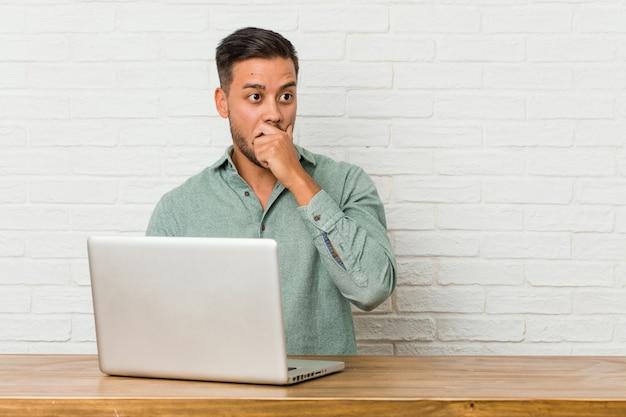 Sitzendes arbeiten des jungen philippinischen mannes mit seinem laptop entsetztes zeigen mit den zeigefingern auf einen kopienraum. Premium Fotos