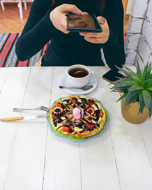 Sitzendes caffe des jungen mädchens, das frühstückswaffel mit schokoladensoße, bananenscheiben und erdbeeren auf grüner keramischer platte isst und fotografierte ihr frühstück Kostenlose Fotos