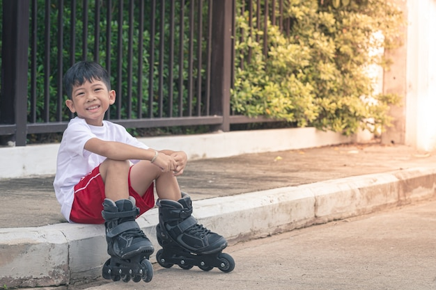 Sitzendes lächeln jungenasiens an den rollerblade-schuhen Premium Fotos