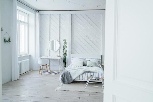 Skandinavischer moderner gemütlicher eco innenraum, weiße tabelle und spiegel im bettraum Premium Fotos