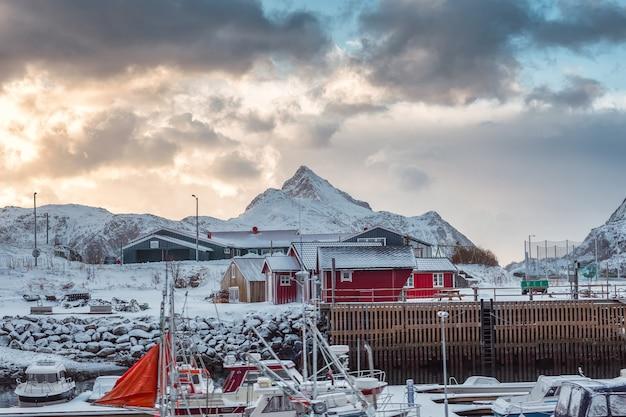 Skandinavisches dorf mit fischerboot und schneeberg in der küstenlinie Premium Fotos