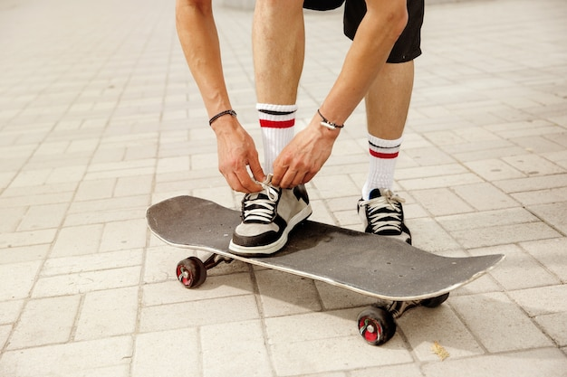 Skateboarder, der sich darauf vorbereitet, an einem wolkigen tag auf der straße der stadt zu fahren. junger mann in turnschuhen und mütze mit einem longboard auf dem asphalt. konzept von freizeitbeschäftigung, sport, extrem, hobby und bewegung. Kostenlose Fotos