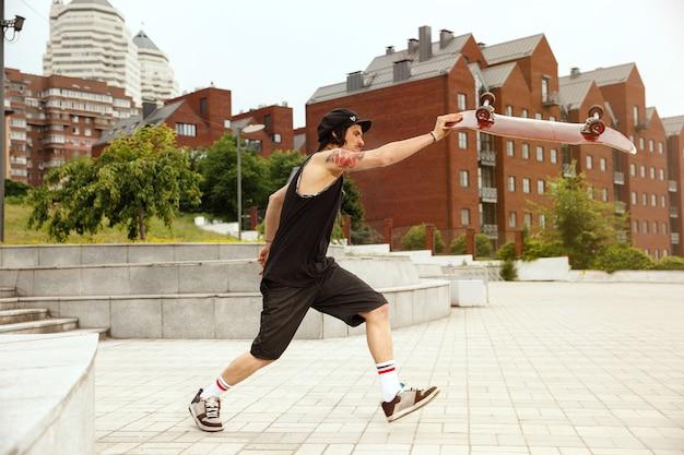 Skateboarder machen an bewölkten tagen einen trick auf der straße der stadt. junger mann in turnschuhen und mütze reiten und longboarding auf dem asphalt. konzept von freizeitbeschäftigung, sport, extrem, hobby und bewegung. Kostenlose Fotos