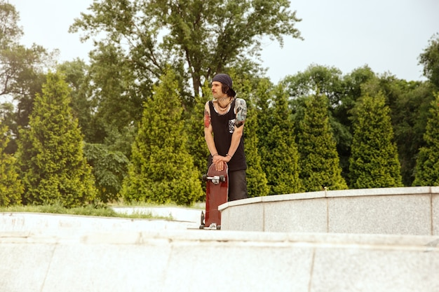 Skateboarder ruht sich aus, nachdem er an einem wolkigen tag auf der straße der stadt gefahren ist. junger mann in turnschuhen und mütze mit einem longboard auf dem asphalt. konzept von freizeitbeschäftigung, sport, extrem, hobby und bewegung. Kostenlose Fotos
