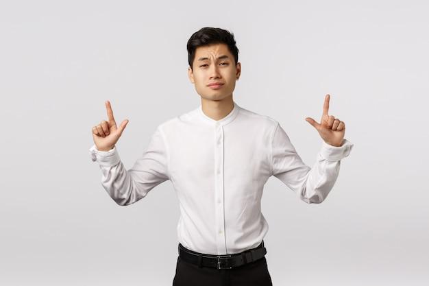 Skeptisch attraktiver asiatischer geschäftsmann haben die zweifel und oben zeigen, die mit dem unglauben oder dem zögern die stirn runzeln, das urteilsvermögen grinsen und verachten, glauben nicht, dass dieses produkt seine aufmerksamkeit wert ist Premium Fotos