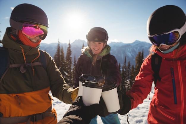 Skifahrer, die eine tasse kaffee auf einem schneebedeckten berg rösten Kostenlose Fotos