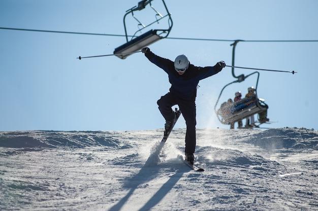 Skifahrer im moment auf die schneebedeckte piste fallen Premium Fotos