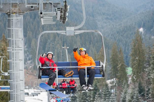Skifahrer und snowboarder, die oben auf skilift fahren Premium Fotos