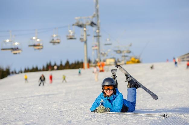 Skifahrermädchen, das auf dem schnee am skiort an einem sonnigen tag liegt Premium Fotos