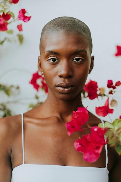 Skinhead frau umgeben von roten blumen Premium Fotos