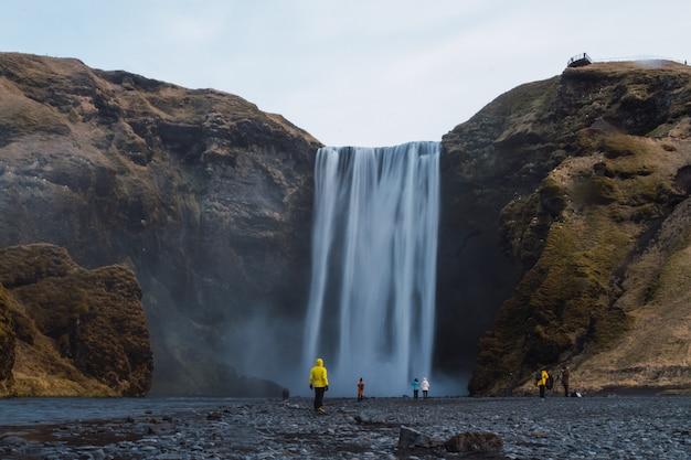 Skogafoss wasserfall umgeben von menschen und felsen unter einem bewölkten himmel in island Kostenlose Fotos
