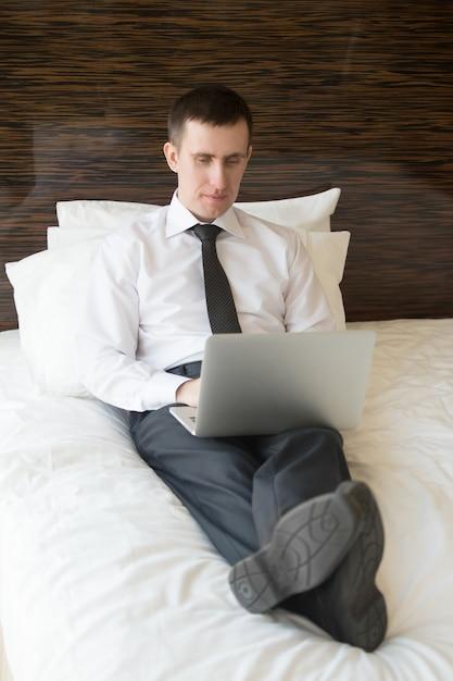 smart mann auf einem laptop im bett liegend typisierung download der kostenlosen fotos. Black Bedroom Furniture Sets. Home Design Ideas
