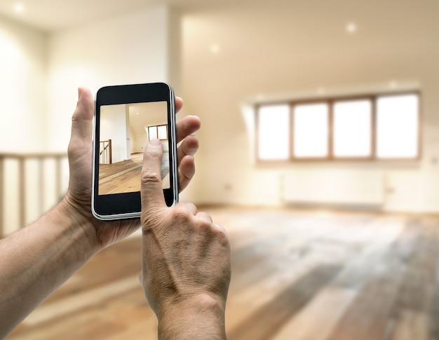 Smarthphone mit der mannhand, die foto im modernen dachboden macht Premium Fotos