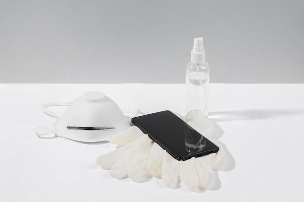 Smartphone auf der oberfläche mit gesichtsmaske und op-handschuhen Kostenlose Fotos