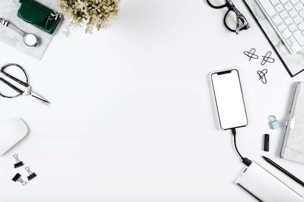 Smartphone, das auf arbeitsplatz mit bürowerkzeugen auflädt Kostenlose Fotos