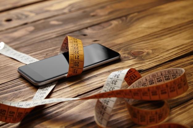 Smartphone gebunden in schneiderei meter präsentiert auf rustikale holztisch nahansicht Kostenlose Fotos