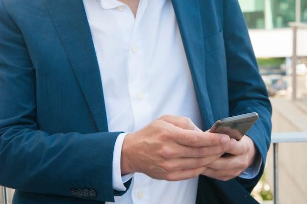 Smartphone in den geschäftsmannhänden Kostenlose Fotos