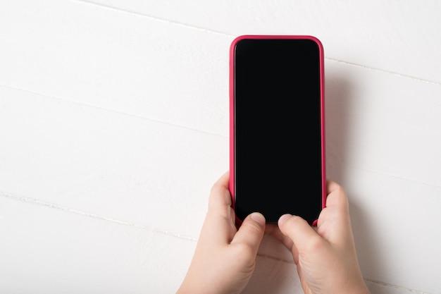 Smartphone in den händen der kinder auf einem hellen hintergrund Premium Fotos