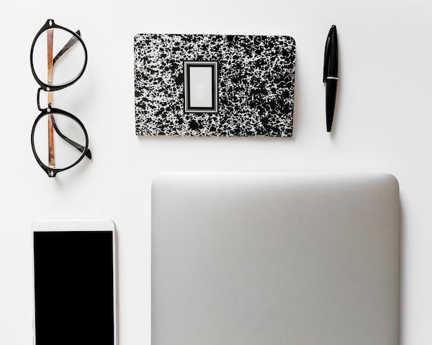 Smartphone in der nähe von notebook, brille und stift Kostenlose Fotos