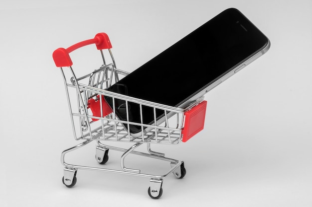 Smartphone in einem einkaufswagen Premium Fotos