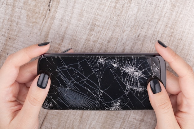 Smartphone mit einem kaputten bildschirm in der hand des mädchens Premium Fotos