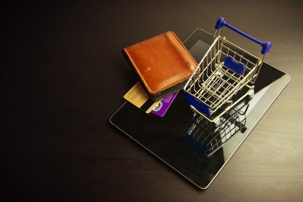 Smartphone mit einkaufswagen auf holz Premium Fotos