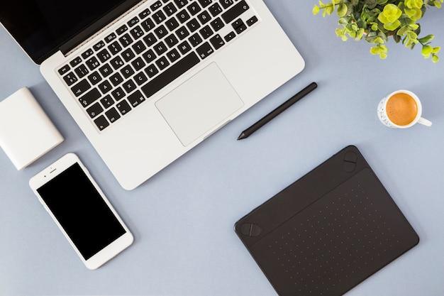 Smartphone mit laptop, kaffeetasse und notizbuch Kostenlose Fotos