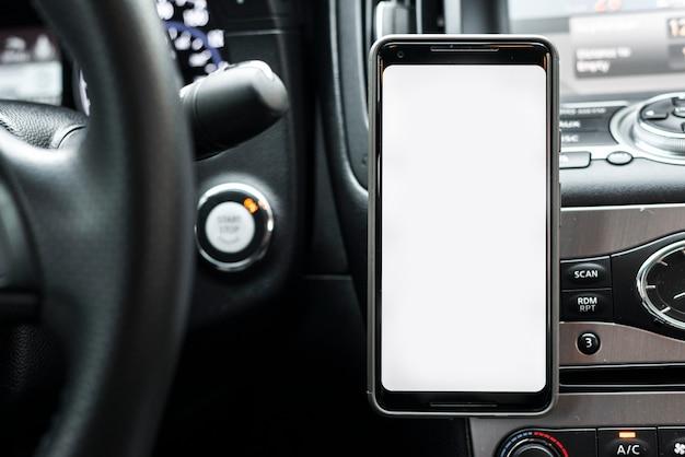 Smartphone mit weißer bildschirmanzeige auf dem armaturenbrett des autos Kostenlose Fotos