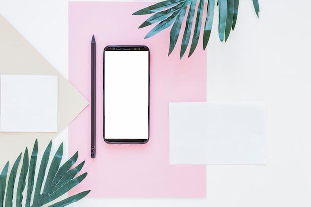 Smartphone nahe papieren und palmen auf weißem schreibtisch Kostenlose Fotos