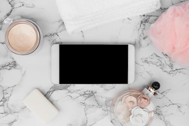 Smartphone; parfümflasche; handtuch; seife; feuchtigkeitscreme und luffa auf marmorhintergrund Kostenlose Fotos