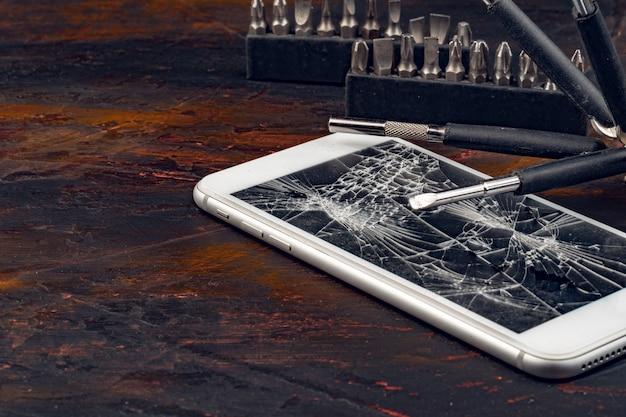 Smartphone-reparaturkonzept. beschädigtes display von smartphone und werkzeugen Premium Fotos