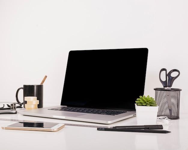 Smartphone und laptop mit leerem schwarzem bildschirm auf schreibtisch Kostenlose Fotos