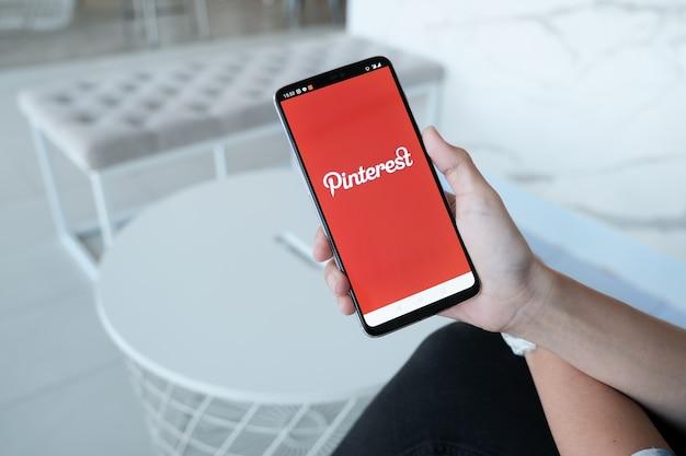 Smartphone zeigt pinterest-anwendung auf dem handy. es wurde von menschenhand im café-laden gehalten. Premium Fotos