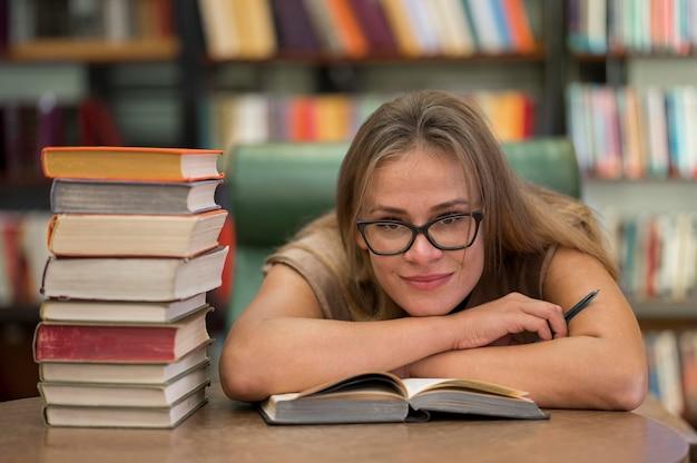 Smiley-frau, die an der bibliothek studiert Kostenlose Fotos
