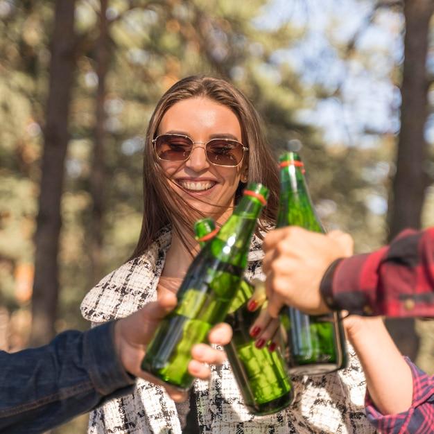 Smiley-frau, die bier mit ihren freunden draußen röstet Kostenlose Fotos