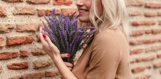 Smiley-frau, die blumenstrauß des lavendels hält Kostenlose Fotos