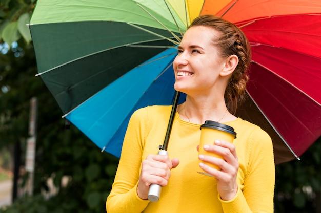 Smiley-frau, die eine tasse kaffee unter einem bunten regenschirm hält Kostenlose Fotos