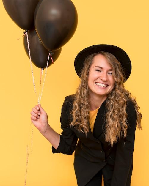 Smiley-frau, die einen hut trägt und luftballons hält Kostenlose Fotos