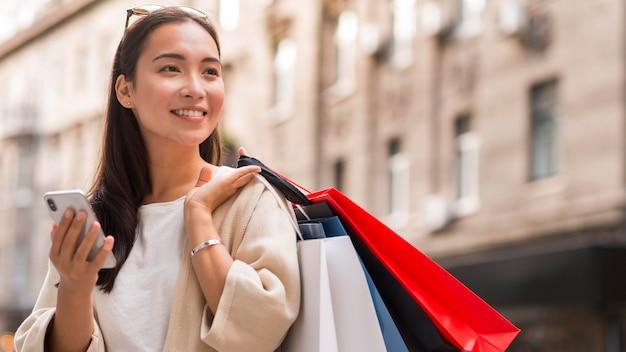 Smiley-frau, die einkaufstaschen und smartphone draußen hält Kostenlose Fotos