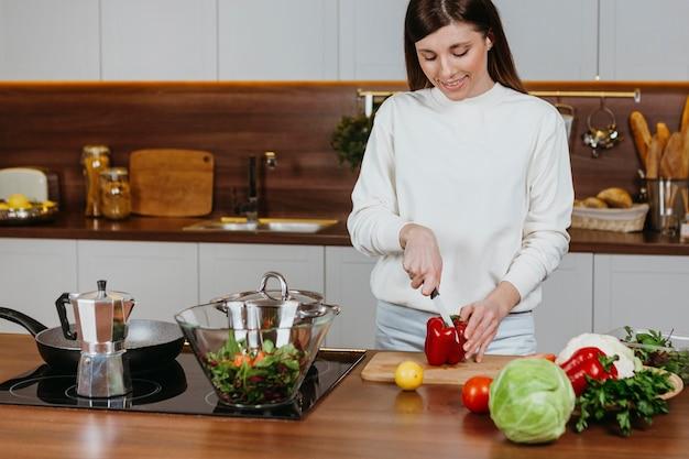 Smiley-frau, die essen in der küche zu hause zubereitet Kostenlose Fotos