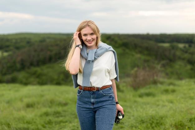 Smiley-frau, die in der natur beim halten der kamera aufwirft Kostenlose Fotos