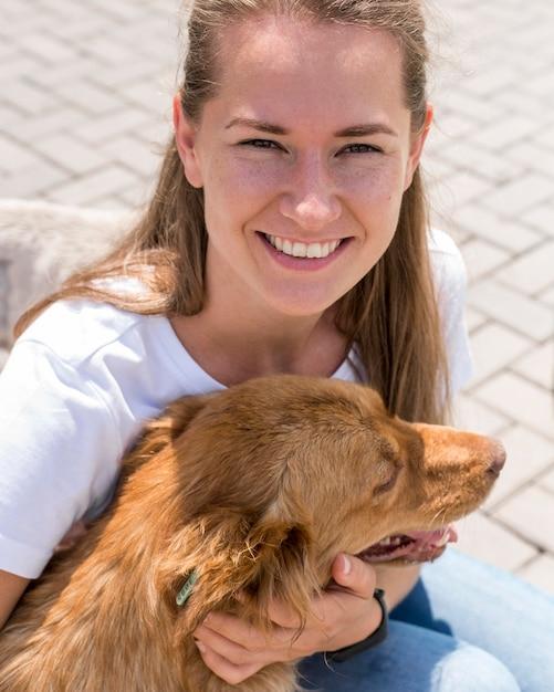 Smiley-frau, die mit hund im schutz spielt Kostenlose Fotos