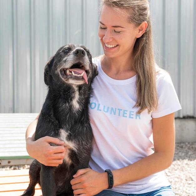 Smiley-frau, die mit niedlichem rettungshund aufwirft Kostenlose Fotos