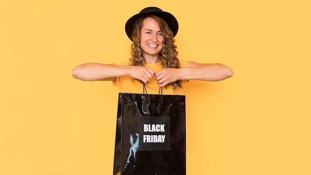 Smiley-frau, die schwarze freitag-einkaufstasche hält Kostenlose Fotos